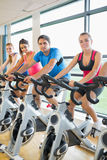 Four people working out at spinning class Stock Image