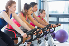 Four people working out at spinning class Stock Images