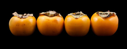 Four persimmon fruits Stock Photo