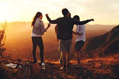 Four Person Standing at Top of Grassy Mountain royalty free stock photo