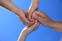 Four persons holding hands. In front of bright blue sky Royalty Free Stock Image