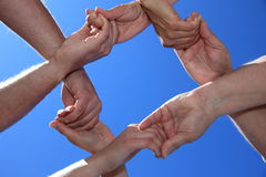 Four persons showing loyalty. Four persons holding hands in front of bright blue sky Royalty Free Stock Image