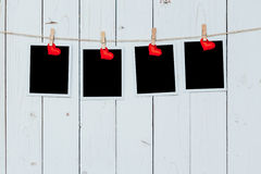 Four photo frame blank and red heart hanging on white wood backg Royalty Free Stock Photography