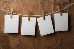 Four photo paper attach to rope with clothes pins. On paper background Royalty Free Stock Photography