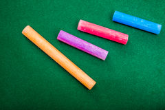 Four pieces of chalk on green Royalty Free Stock Image