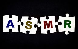 Four pieces of puzzle with letters ASMR on black background. Close-up royalty free stock photography