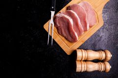 Four pieces of raw steaks meat on wooden board next to two salt. And pepper shakers on black wooden backgorund Royalty Free Stock Image