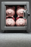Four piggy banks in safe Royalty Free Stock Photography