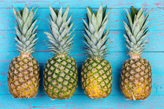 Four pineapples beside each other on table Stock Images