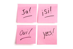 Four pink postits in four languages. Pink post it notes isolated on white with ja', si, oui, and yes written Royalty Free Stock Photo