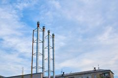 Four pipes from the boiler room against the blue sky with clouds. royalty free stock images