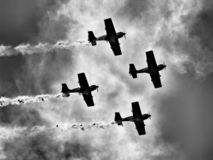 Four piston propeller aerobatic aicraft against sun. stock photography