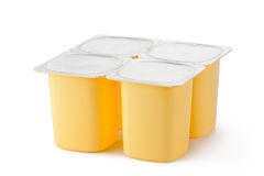 Four plastic containers for dairy products. With foil lid. Standing on a white Royalty Free Stock Photography