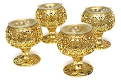 Four plastic golden colored table cup candle holders Royalty Free Stock Photography