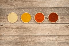 Four Plates Filled with Spices. Four small plates filled with fenugreek, turmeric, chili and paprika on a wooden table Royalty Free Stock Images