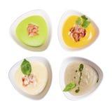 Four plates of soup. Pea soup, pumpkin soup, mushroom soup, soup with prawns Stock Images