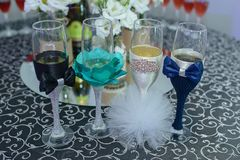 Four playfully decorated flute glasses for a wedding, with bow ties and pom poms resembling the bride and groom outfits. Horizontal shot of full champagne or Royalty Free Stock Images