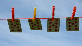 Four playing cards on clothes-line and wind stock video footage