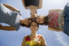 Four playmates, head to head. Four friends on the blue sky Royalty Free Stock Images