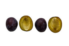 Four plum halves, two turned upside-down. Isolated on white background Royalty Free Stock Photography