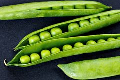 Four pods of green peas lying on a black background Stock Photos