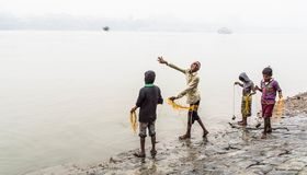Poor children. Four poor children throwing magnet tied to a rope into river ganges to collect coins stock image