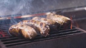Four Pork juicy pork sausages are fried on a hot grill.   slow motion.  stock video footage