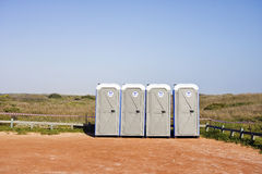 Four portable toilets in gravel parking lot. Landscape exterior Royalty Free Stock Image