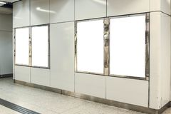 Four portrait orientation blank mock up advertisement light boxes at a metro station.  Stock Photos