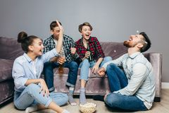 Four positive people enjoy time at home. Competition with a popcorn. funny time with old friends stock photos