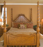 Four Poster Bed. In golden bedroom Stock Images