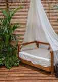 Four-poster bed on a wooden porch Stock Photos
