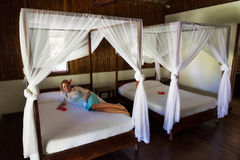 Four-poster vacation bed. Four-poster beds on vacation with a beautiful woman laying on one of them Stock Photo