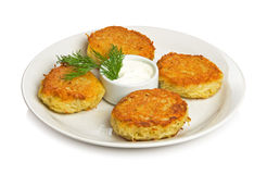 Four potato cakes. On a white plate with a sour cream and dill. Isolated on white. Isolated by clipping path Stock Images