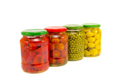 Four potted vegetables glas jars isolated on white Royalty Free Stock Photos