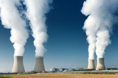 Four power plant cooling towers steaming. On dark blue sky background stock photography