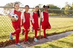 Four pre teen girls in a soccer team looking to camera stock photography