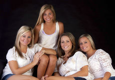 Four pretty sisters. Four pretty blond sisters sitting together on a couch royalty free stock photos
