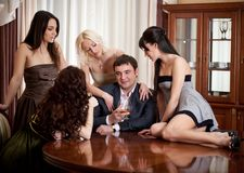Four pretty women seduce one man. In a room Stock Photography