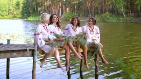 Pretty women in ethnic dresses with floral circlets sitting on wooden bridge. Four pretty women in traditional ukraininan dresses with floral circlets sitting on stock footage