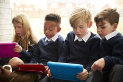 Four primary school children sitting on the floor in front of a window using tablet computers during break time, close up royalty free stock images