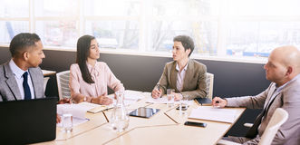 Four professional executives conducting a early morning business meeting. Four business executives integrate technology in a meeting early in the morning at the stock photos