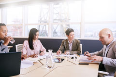 Four professional executives conducting a early morning business meeting. Four business executives integrate technology in a meeting early in the morning at the royalty free stock photography