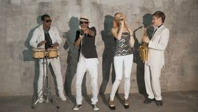 Four professional musicians dance and sing. Beautiful young blond woman and African man singing. The white musician plays the saxophone, an African man plays stock footage