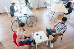 Four proficient freelancers and independent contractors co-worki. Ng on tablets and laptops connected to internet, at a shared desk behind a commuter bike in a royalty free stock photography