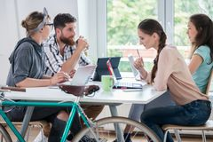 Four proficient freelancers and independent contractors co-worki. Ng on tablets and laptops, connected to internet at a shared desk behind a commuter bike in a stock photo