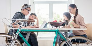 Four proficient freelancers and independent contractors co-working. On tablets and laptops, connected to internet at a shared desk behind a commuter bike in a stock photos