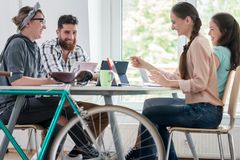 Four proficient freelancers and independent contractors co-working. On tablets and laptops, connected to internet at a shared desk behind a commuter bike in a royalty free stock photography