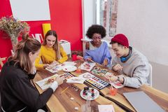 Four promising art students using paints while drawing. Using paints. Four promising art students using paints while drawing their exam task together royalty free stock photo