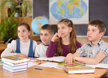 Four pupils in classroom Stock Images